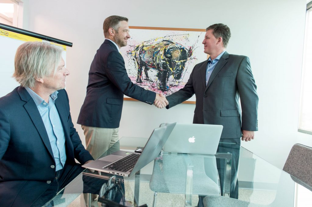 Commercial Broker and Tenant Shaking Hands After Successful Lease Terms Negotiation - Transworld Commercial Real Estate